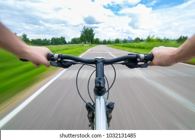 Rider driving bicycle on an asphalt road.