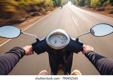 Rider driving scooter on an asphalt road. Motion blurred background. First-person view