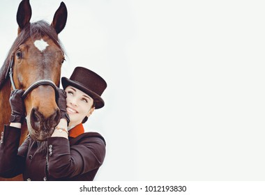 Rider elegant woman talking to her horse. Portrait of riding horse with woman in hat. Equestrian horse with rider and old stable in background.