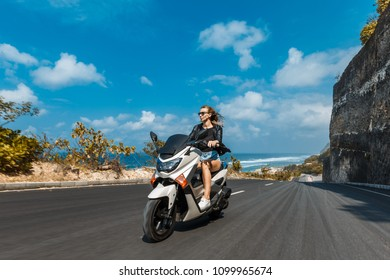 Rider Female on the scooter in motion. Woman riding on the motorbike on embankment on the Bali, road near beach.