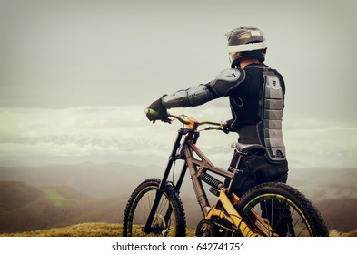 The rider in the full-face helmet and full protective equipment on the mtb bike stands on a rock against the background of a ridge and low clouds