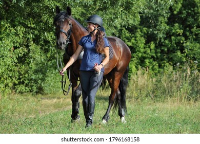 Rider girl with the horse walking in outdoors
