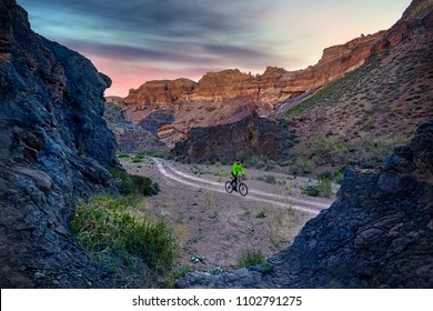 Rider in green jacket at mountain bike in the desert Charyn Canyon at sunrise in Kazakhstan. Extreme Sport Concept.