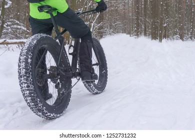 Rider in green sport jacket on a fat bike. Riding on a fat tyres. Big wheel cycling