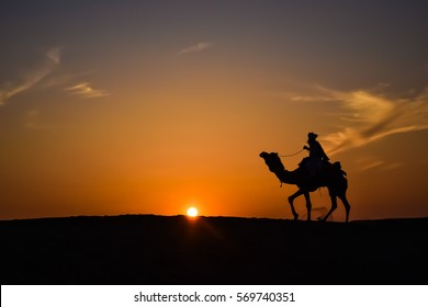 Rider with his Camel returning to home in the evening.