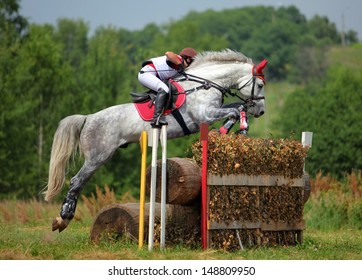 Rider jumping with horse over obstacle