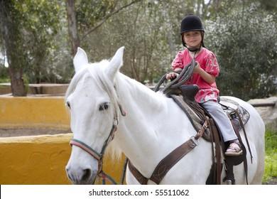 rider little girl jockey hat white horse outdoors park