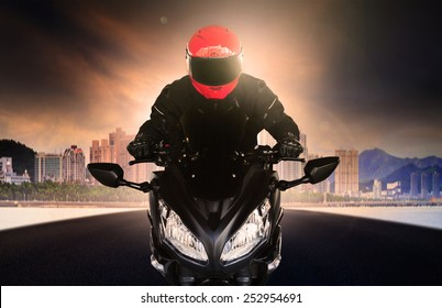 rider man wearing safety suit and anti knock helmet riding big motorcycle on asphalt street against urban and sky scrapper use for people activities and transportation theme