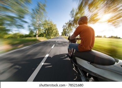 rider on motorcycle riding in parkway - nature