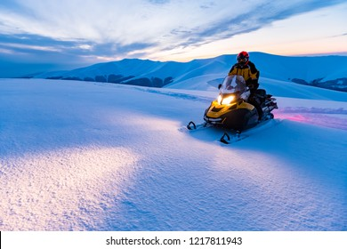 Ein Fahrer auf dem Schneemobil. Schöner Wintertag in den ukrainischen Bergen.Sonnenuntergang.