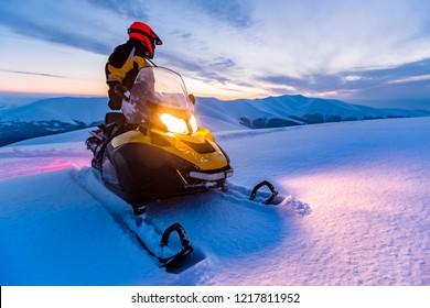 Ein Fahrer auf dem Schneemobil. Schöner Wintertag in den ukrainischen Bergen. Sonnenuntergang.