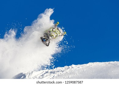 rider on a snowmobile in a jump in the air upside down. from left to right, long trail of big snow storm. winter mountain valley