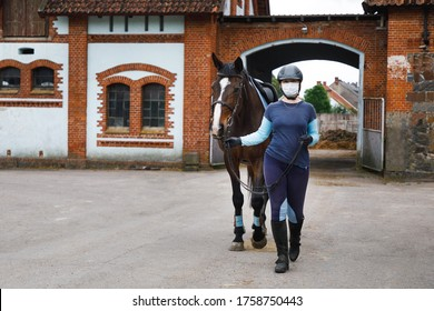 Rider in a sanitary mask with the horse in summer