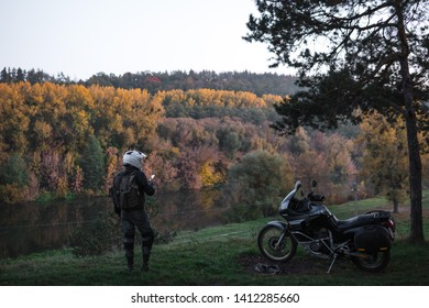 Rider standing with adventure motorcycle, Motorcyclist gear, A motorbike driver looks, active lifestyle, enduro travel road trip. Evening, autumn. Tourist traveler. copy space, use gadget, enternet