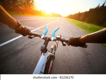 Rider's hands in gloves on a bicycle handlebar. Motion blurred asphalt road