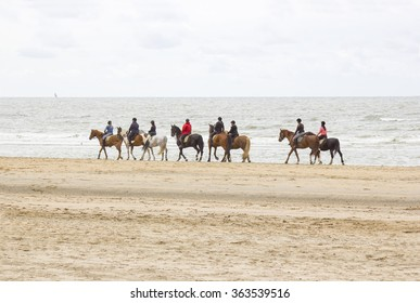 riders on horses on the beach close to North sea