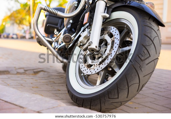 Riders will love. Cropped shot of the shot of the motorcycle forks, tire and front wheel. Disk brake system on a motorcycle. Freedom and travel concept. motorcycle parked on a street.