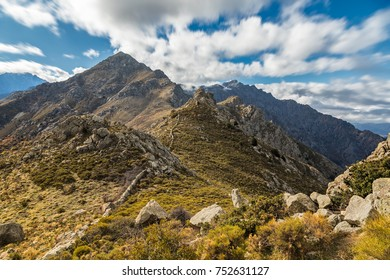 Ridge and ancient stone wall leading to the rugged peak of Monte Parteo in the mountains of the Balagne region of Corsica