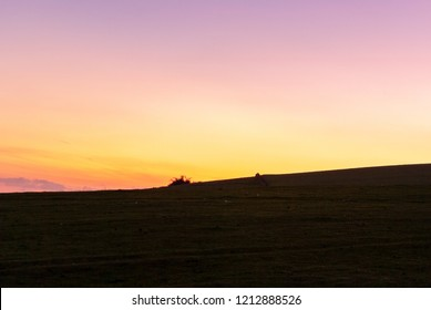 Ridgeline on the South Downs as dawn breaks with orange and pink glow