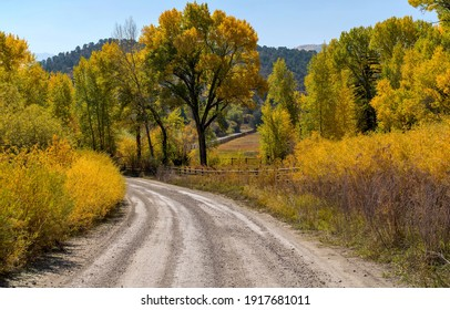 Ridgway, Colorado, USA - October 6, 2020: Autumn morning view of a back country road winding through a mountain ranch. County Road 9, aka West Dallas Road, at Ralph Lauren's Double RL Ranch.