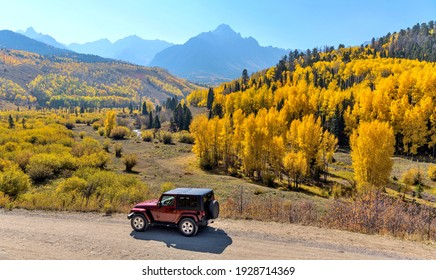Ridgway, Colorado, USA - October 7, 2020: A red Jeep exploring in a colorful valley at base of rugged Sneffels Range on a bright sunny Autumn morning.