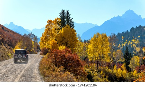Ridgway, Colorado, USA - October 7, 2020: A SUV driving on a scenic backcountry road winding towards rugged Sneffels Range on a sunny Autumn morning in Uncompahgre National Forest.
