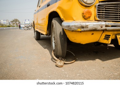 Ridiculous homemade yellow taxi theft protection in India. humorous, hilarious, comic concept of safety and protection against theft of the car. punctured tire. car tire puncture. prick