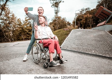Ridiculous selfie. Positive coupe of disabled man and optimistic woman smiling and making funny faces while taking photos