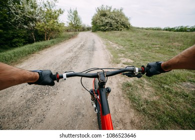 Riding a bike first person perspective with two male hands in gloves holding bicycle handlebar. Sports, tourism and activity concept