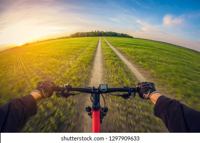 Riding bike on dirt road in field at sunset, first-person view, distortion perspective fisheye lens
