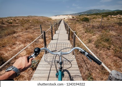 Riding a bike on the path to Guincho Beach in Portugal made on sand dunes