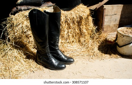 Riding boot in the stable, hay background