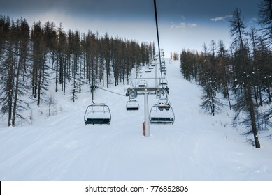 Riding the Chair Lift through the Forest of the High Alpine with Snow Covered Trees