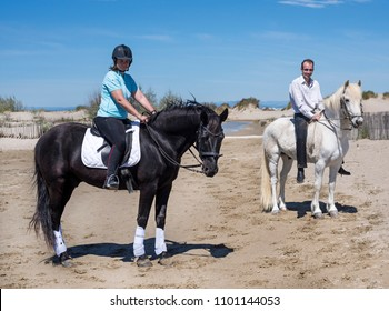 riding couple and their stallions on the beach