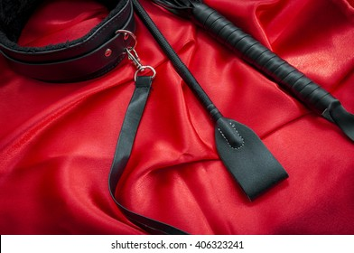 Riding crop, a whip flogger, leather choker and leash on red satin, kinky sex toys for dom / sub sexual and other forms of kink