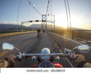 Riding a cruiser motorcycle on Lions Gate Bridge towards North Vancouver, British Columbia, Canada. Taken during a sunny summer sunrise.