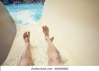Riding down a slide at a waterpark resort. Point of view photo of a men going down a waterslide at an outdoor waterpark during a warm summer day.
