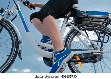 Riding e-bike or electric bicycle, shot against blue sky, clean air concept