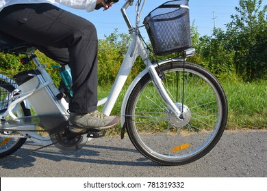 Riding e-bike or electric bicycle, shot from below, ecology concept. E bike cyclist  riding through a park green area. Close up of battery of an ebike.