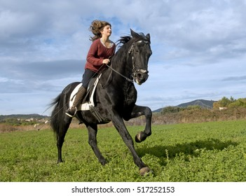 riding girl and black stallion in the nature