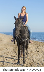riding girl with her black  on the beach