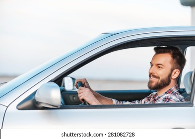 Riding his new car. Side view of handsome young man driving his car and smiling