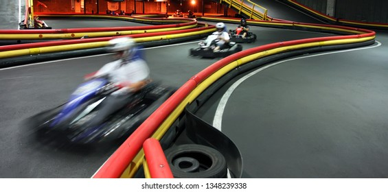 Riding in kart indoors at high speed. Active leisure, entertainment on the karting track
