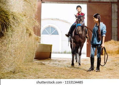 Riding lesson. Professional beautiful horsewoman teaching her cute daughter riding racing horse