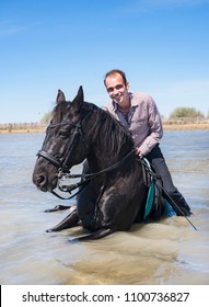 riding man and his stallion on the beach