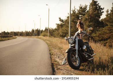 Riding a motorcycle. A beautiful girl is sitting on a motorcycle. Day. Background blue sky, forest, road. In short black shorts and a white T-shirt. Straightens her hair and looks at the sunset.