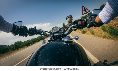 Riding an old black motorbike under a blue sunny sky driver point of view