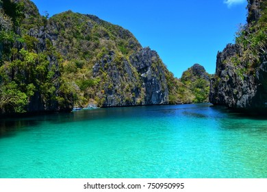 Riding on a boat between tropical island rocks on the turquoise sea