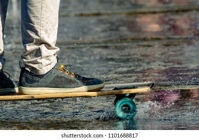 Riding on skateboard in through fountain. View of feet on skateboard