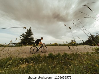 Riding a racing bicycle in Tuscany on summer. Cloudy sky
